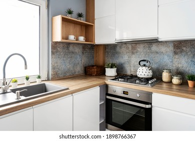 Small white kitchen with stylish tiles, wooden cabinets and sink with faucet near the window. Scandinavian interior of room in apartment.