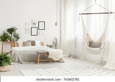Small white lampshade hanging in bright room with hammock, king size bed and posters