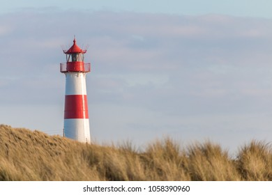 Small white lighthouse on a hill with beach grass on Sylt island, Germany