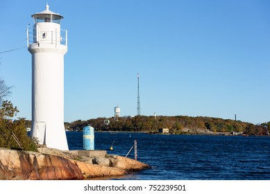 Small white lighthouse on the Karlskrona (Sweden) archipelago island of Stumholmen with coastal landscape in background. Water tower and radio antenna on island behind lighthouse.