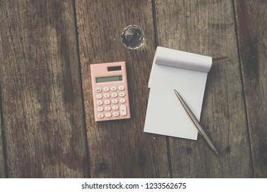 Small white notebook and calculator on old grunge wood texture background.