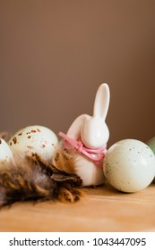 Small white rabbit figurine with easter eggs and feathers nest on pastel background