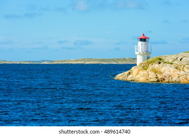 Small white and red lighthouse on cliff in barren Swedish west coast archipelago.