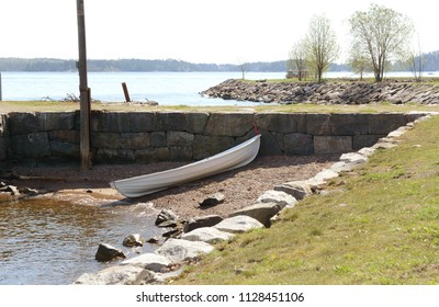 Small white rowboat on a small stony area of shore, against a stone wall on Suomenlinna island, Finland
