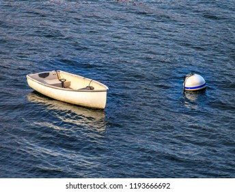 A small white rowboat skiff sits in the water attached by rope to a large round float. The water is blue green and has small waves.
