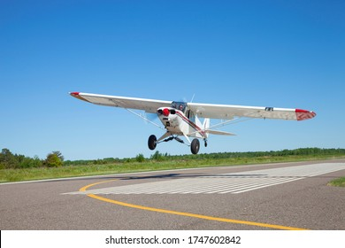 Small white single engine airplane takes off from a municipal airfield in rural Minnesota