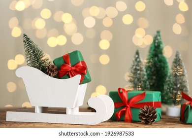 Small white sleigh, decorative Christmas trees and gift boxes on wooden table against blurred lights