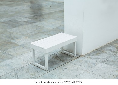Small white step stool on tiled floor in empty hall
