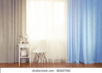 Small white table with lamp and chair on curtain background