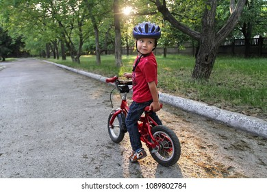 A small white Toddler boy in a protective helmet on his head sits on a children's bicycle. Toddler on a two-wheeled red bicycle looks back. A sly smile on the child's face