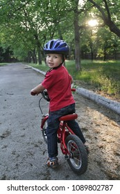 A small white Toddler boy wearing a protective helmet on his head is riding a baby bike. Toddler on a two-wheeled red bicycle.
