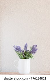 Small white vase with bouquet of lavender flowers.