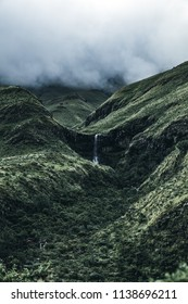 A small white waterfall flowing down green moss covered hills with heavy fog and clouds on top of the mountain on a moody misty cloudy day in South Africa