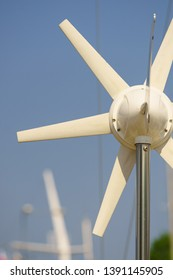 Small white windmill fan generating electricity from wind on yacht. Renewable sources