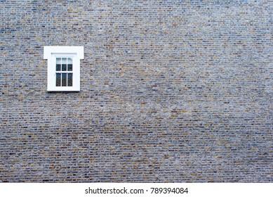 Small white window on a big brick empty wall
