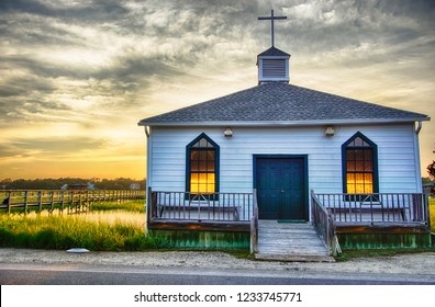 small white wooden chapel on the water on the coast during a colorful summer sunset