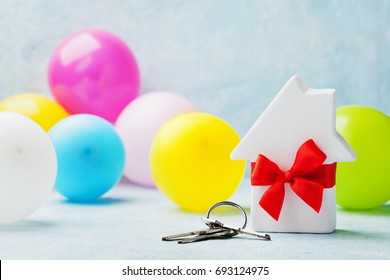 Small white wooden house decorated red bow ribbon with bunch of keys and balloons on light background. Housewarming, gift, moving, real estate or buying a new home concept.