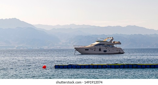 a small white yacht is anchored in the gulf of eilat akaba in israel with the mountains of jordan in a hazy background