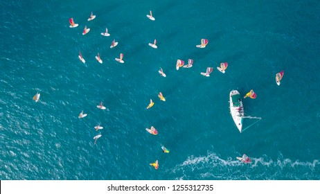 Small white yacht surrounded by a large group of Wind surfers - Top down aerial image.