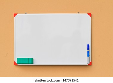 Small whiteboard on yellow concrete wall with large space for your copy text (announcement, offer, menu)