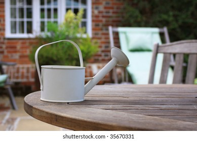 A small white/cream watering can set atop a wooden patio table in front of a stone faced country cottage in soft focus to the background.