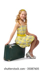 small white-headed girl in a yellow dress with a suitcase