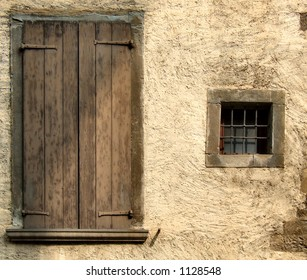 Small window and big closed window with brown shutters. Rough, yellow or beige wall of an old house in a small Italian town or village.