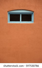 Small window with blue border in a tan wall