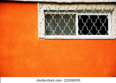 Small window with a grille and mosquito screen on the orange textured wall. Beersheba, Israel.
