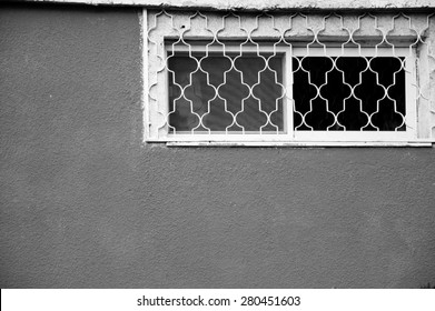 Small window with a grille and mosquito screen on stucco textured wall. Beersheba, Israel. Aged photo. Black and white.