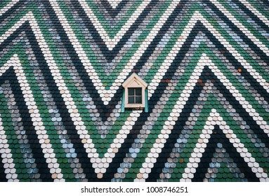 Small window on on the wall painted with blue, green and white stripes in zigzag. St. Stephen's Cathedral, Vienna, Austria. Minimalism concept