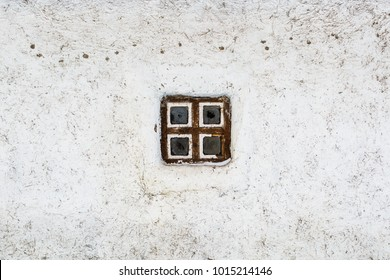A small window in a white adobe wall. Fragment of the old Cossack house made of clay. Texture.