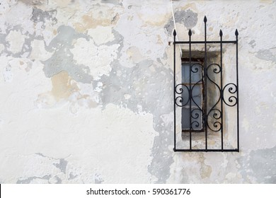 small window with a wrought iron grid against a textured wall.