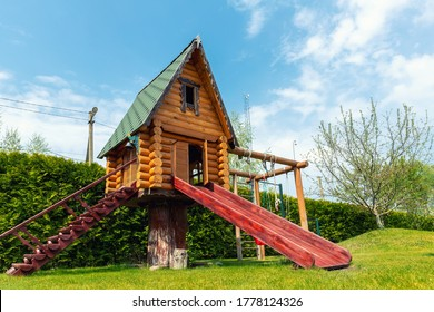Small wood log playhouse hut with stairs ladder and wooden slide on children playground at park or house yard. Green grass lawn garden and blue clear sky in background on bright sunny summer day