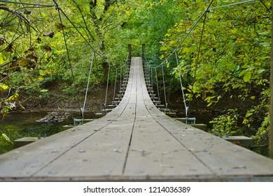 Small wood pedestrian suspension bridge with steel cables over a river in the woods in Princeton, New Jersey