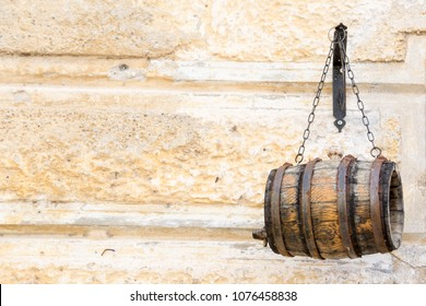 Small wooden barrel hanging on metal chains