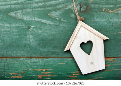 Small wooden bird house with heart decoration on green retro wooden background, copy space.