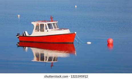 Small wooden boat and buoys in calm blue water.