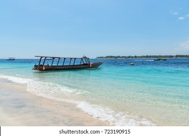 Small wooden boat on blue beach with cloudy sky and Lombok island on background. Gili Trawangan, Indonesia.