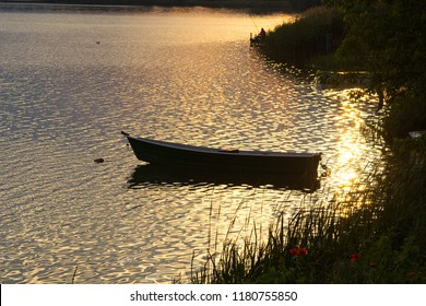 A small wooden boat on the lake in the rays of the setting sun