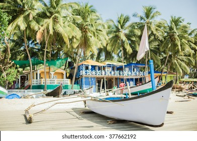 Small wooden boat resting in the colorful beach of cool tropical resort of Goa, India