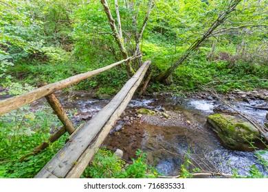 small wooden bridge across a rushing mountain river
