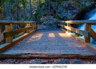 a small, wooden bridge in front of a waterfall in the bavarian forest