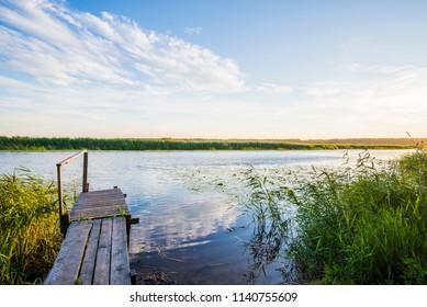 A small wooden bridge near the lake. Summer sunset, Latvia