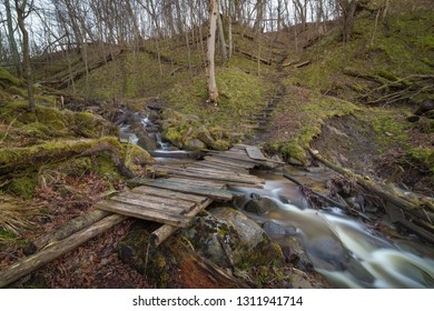 Small wooden bridge over a fast stream deep in the forest.