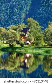 Small wooden bungalow on bank of bay on South part of Lake Teletskoye in the mouth of the river Chulyshman in Altay mountains