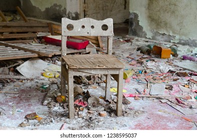 Small wooden chair among dirt and debris in abandoned kindergarten, dead city of Pripyat, Chernobyl NPP exclusion zone, Ukraine
