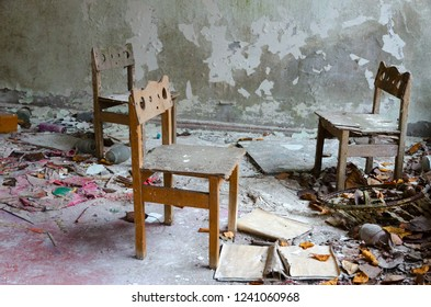 Small wooden chairs among dirt and debris in abandoned kindergarten, dead city of Pripyat, Chernobyl NPP exclusion zone, Ukraine