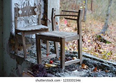 Small wooden chairs by window without glass in kindergarten against background of forest overgrown street, Pripyat, Chernobyl NPP alienation zone, Ukraine