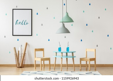 Small wooden chairs and table set for kids and mock-up poster on a white wall with wallpaper in a preschool room interior with blue and green elements